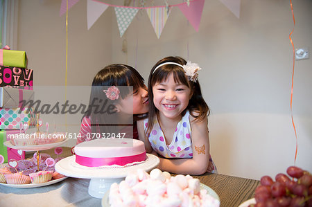 Girl kissing friend at birthday party Stock Photo - Premium Royalty-Free, Image code: 614-07032047