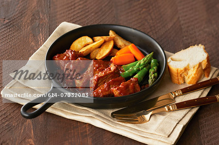 Still life of pan with meat, chips and vegetables Stock Photo - Premium Royalty-Free, Image code: 614-07032083