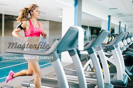 Young woman running on treadmill Stock Photo - Premium Royalty-Free, Image code: 614-07032159