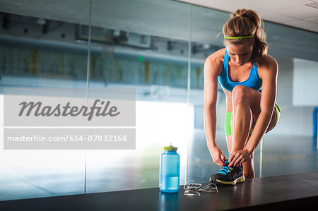 Young woman tying shoelace in gym Stock Photo - Premium Royalty-Free, Image code: 614-07032168