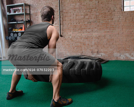Male bodybuilder lifting tyre Stock Photo - Premium Royalty-Free, Image code: 614-07032203