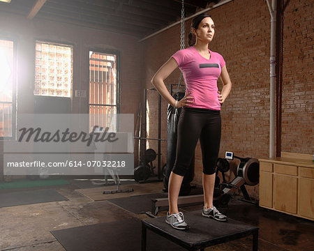 Young woman standing on table in gym Stock Photo - Premium Royalty-Free, Image code: 614-07032218