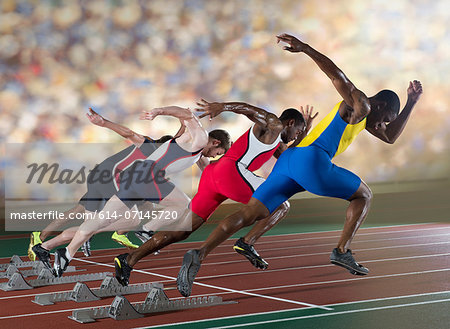 Four athletes starting a sprint race Stock Photo - Premium Royalty-Free, Image code: 614-07145720