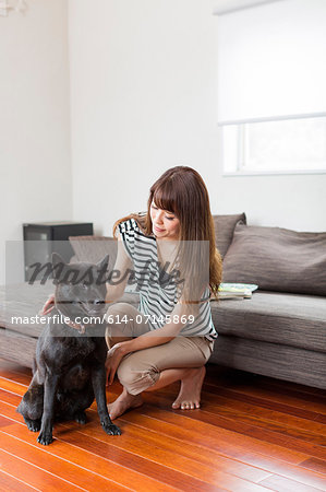Woman with dog in living room Stock Photo - Premium Royalty-Free, Image code: 614-07145869