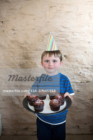 Portrait of boy wearing party hat holding cupcakes Stock Photo - Premium Royalty-Free, Image code: 614-07145923