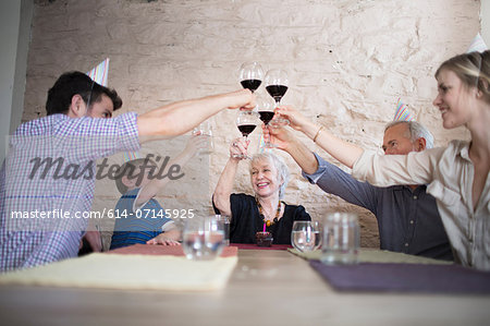 Family toasting with red wine at dinner table Stock Photo - Premium Royalty-Free, Image code: 614-07145925