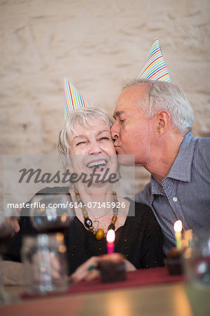 Senior couple wearing party hats, man kissing woman on cheek Stock Photo - Premium Royalty-Free, Image code: 614-07145926