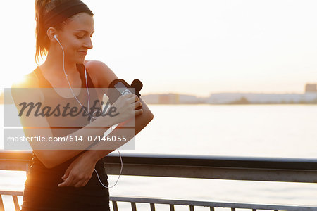 Young female jogger on riverside adjusting MP3 player Stock Photo - Premium Royalty-Free, Image code: 614-07146055