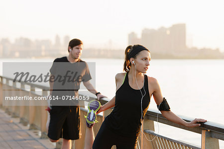 Jogging couple stretching on riverside early morning