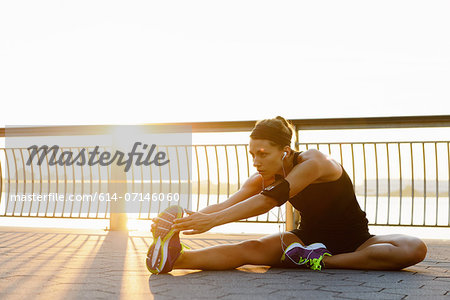 Young female jogger stretching at sunrise Stock Photo - Premium Royalty-Free, Image code: 614-07146060
