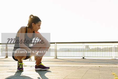 Young female jogger crouching and out of breath Stock Photo - Premium Royalty-Free, Image code: 614-07146072