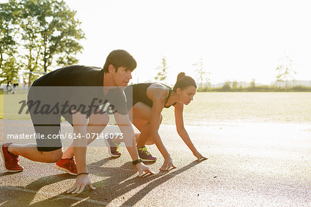 Couple preparing to race in city park early morning Stock Photo - Premium Royalty-Free, Image code: 614-07146073