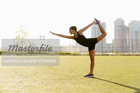 Young female doing yoga stretch in city park Stock Photo - Premium Royalty-Free, Image code: 614-07146078