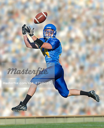 American footballer catching ball Stock Photo - Premium Royalty-Free, Image code: 614-07146105