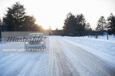 Car driving along road in snow Stock Photo - Premium Royalty-Free, Image code: 614-07146158