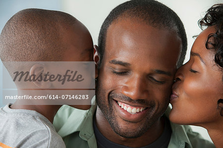 Boy and woman kissing man on cheeks Stock Photo - Premium Royalty-Free, Image code: 614-07146283