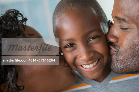 Mother and father kissing son on cheeks Stock Photo - Premium Royalty-Free, Image code: 614-07146284