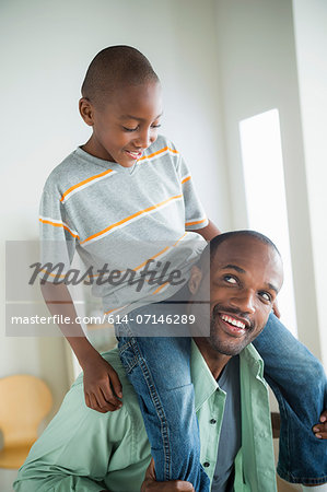 Father giving son piggy back Stock Photo - Premium Royalty-Free, Image code: 614-07146289