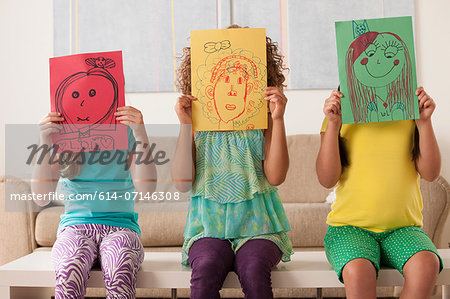 Three girls holding pictures over faces Stock Photo - Premium Royalty-Free, Image code: 614-07146308