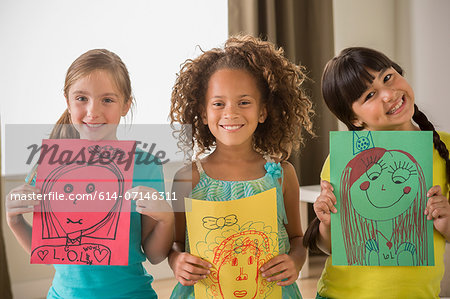 Three girls holding drawings of faces Stock Photo - Premium Royalty-Free, Image code: 614-07146311