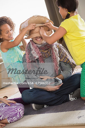 Girls dressing up father Stock Photo - Premium Royalty-Free, Image code: 614-07146312