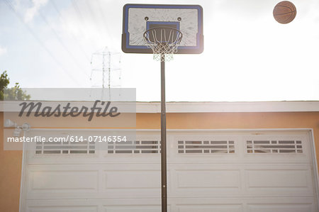 Basketball hoop and ball outside garage Stock Photo - Premium Royalty-Free, Image code: 614-07146354
