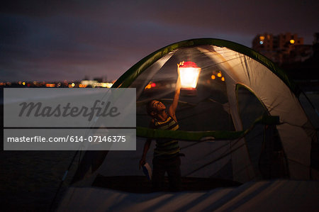 Boy in tent with lap at night, Huntington Beach, California, USA Stock Photo - Premium Royalty-Free, Image code: 614-07146375