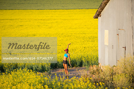 Young woman runner stretching in field of oil seed rape Stock Photo - Premium Royalty-Free, Image code: 614-07146377