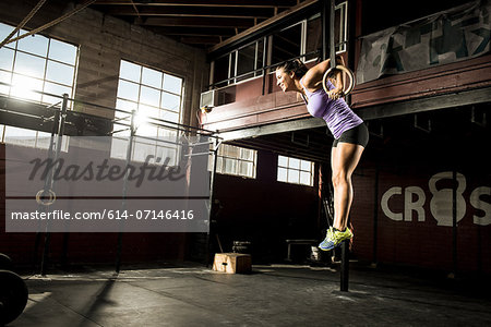 Young woman exercising on gymnastic ring Stock Photo - Premium Royalty-Free, Image code: 614-07146416