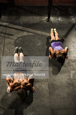 Two young adults doing push ups in gym Stock Photo - Premium Royalty-Free, Image code: 614-07146418