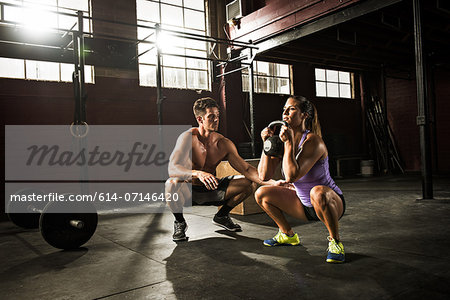 Young woman and personal trainer working out in gym Stock Photo - Premium Royalty-Free, Image code: 614-07146420