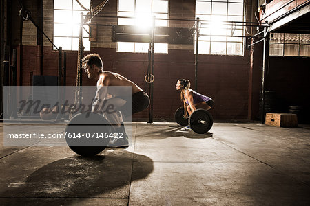Two young adults working out with barbells in gym Stock Photo - Premium Royalty-Free, Image code: 614-07146422