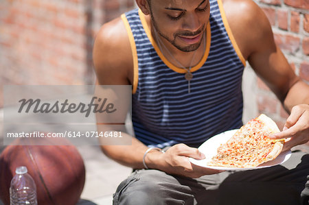 Basketball player with a slice of pizza Stock Photo - Premium Royalty-Free, Image code: 614-07146481