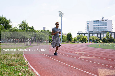 Young man running on outdoor track Stock Photo - Premium Royalty-Free, Image code: 614-07146482