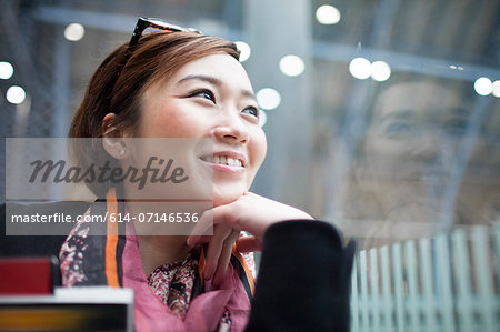 Young woman with hand on chin looking away Stock Photo - Premium Royalty-Free, Image code: 614-07146536