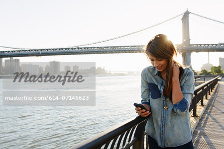 Young woman using cell phone, Manhattan Bridge, Brooklyn, USA Stock Photo - Premium Royalty-Free, Image code: 614-07146623