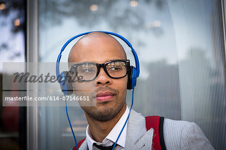 Portrait of young man with shaved head wearing headphones Stock Photo - Premium Royalty-Free, Image code: 614-07146651