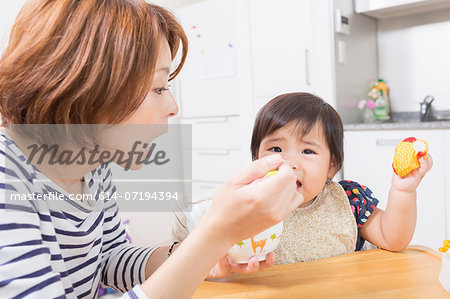 Mother feeding baby in kitchen Stock Photo - Premium Royalty-Free, Image code: 614-07194394