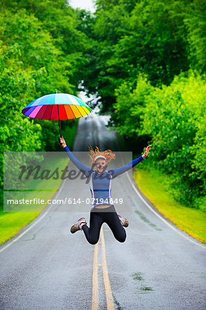 Teenage girl jumping with umbrella on road, Bainbridge Island, Washington, USA Stock Photo - Premium Royalty-Free, Image code: 614-07194649