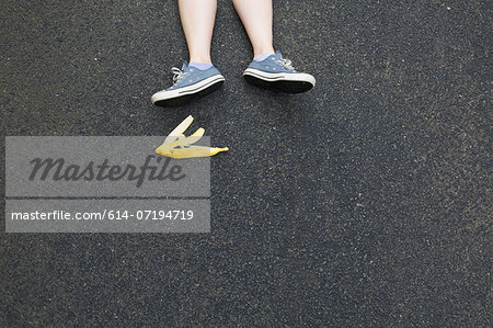 Pair of legs and banana skin on tarmac Stock Photo - Premium Royalty-Free, Image code: 614-07194719