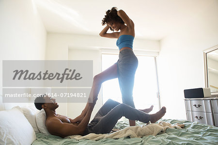 Young woman standing on bed with man lying down Stock Photo - Premium Royalty-Free, Image code: 614-07194821