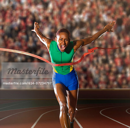 Young woman sprinting through winners tape in stadium Stock Photo - Premium Royalty-Free, Image code: 614-07234797