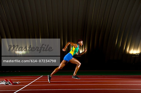 Young woman sprinting in stadium Stock Photo - Premium Royalty-Free, Image code: 614-07234798