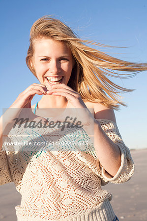 Smiling woman making heart sign with hands, Breezy Point, Queens, New York, USA Stock Photo - Premium Royalty-Free, Image code: 614-07234843
