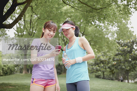 Female friends looking at cellphone in park