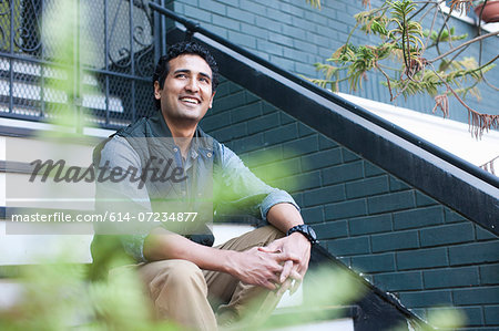 Portrait of young man sitting on steps Stock Photo - Premium Royalty-Free, Image code: 614-07234877