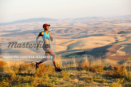 Young woman running on hill, Bainbridge Island, Washington State, USA Stock Photo - Premium Royalty-Free, Image code: 614-07234908