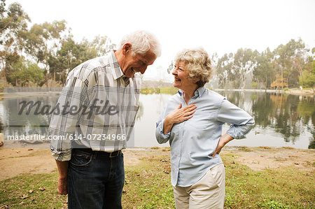 Husband and wife sharing joke by the lake Stock Photo - Premium Royalty-Free, Image code: 614-07234966