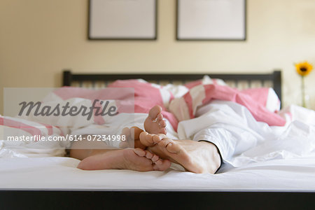 Surface level image of young couple in bed, feet out of duvet Stock Photo - Premium Royalty-Free, Image code: 614-07234998