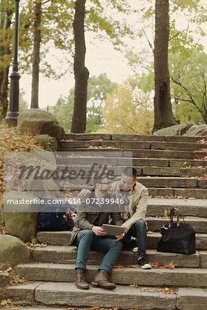 Gay couple using digital tablet on steps Stock Photo - Premium Royalty-Free, Image code: 614-07239946